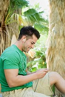 Hispanic man listening to mp3 player in tropical area
