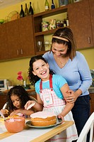 Hispanic mother and daughters baking cake