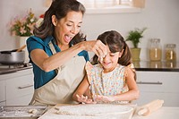 Hispanic grandmother and granddaughter preparing dough