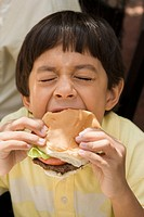 Hispanic boy eating hamburger
