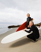 Two senior men holding surfboards at beach
