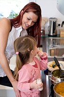 Young woman looking at her daughter in kitchen