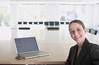 Portrait of businesswoman next to laptop