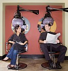 Man and woman under hair dryers in salon