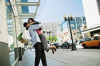 African hugging on sidewalk