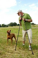 Mature man looking at dog in field