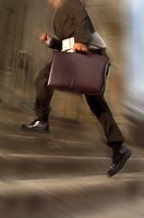 Low section view of business man climbing up stairs in rush