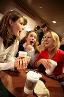 Three teenage girls in cafe