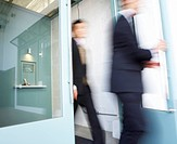 Businesswoman and Businessman Walking Through Door