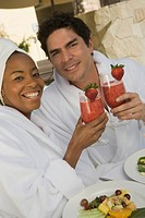 Portrait of couple in bathrobes drinking at health spa
