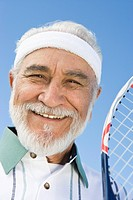 Senior man holding tennis racket portrait