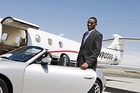 African_American businessman opening door of convertible on landing strip.