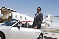 African_American businessman opening door of convertible on landing strip.