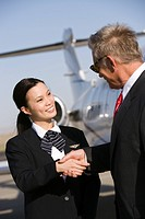Mid_adult flight attendant and senior businessman shaking hands.