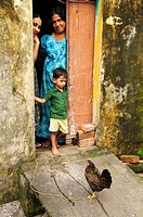 An Indian Family looking out of their home doorway  Fort Cochin, Kerala, India