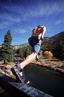 Young man jumping off ledge into the Truckee River California USA