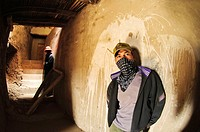 Men wearing masks to protect from the dust of working in a passage at tiksey monastery  Tiksey, Ladakh, India