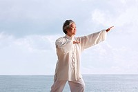 Older woman doing tai chi.
