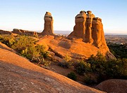 Pillars of sandstone glow in early morning light near Devils Garden in Arches National Park outside Moab, Utah