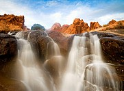 A waterfall cascades below rugged sandstone peaks and a cloud filled sky near Moab, Utah