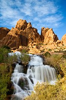 A waterfall cascades below a dramatic sandstone ridge south of Moab, Utah, USA