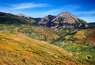 Haystack Mountain presides over hillsides painted in swaths of autumn color in the La Sal mountains near Moab, Utah