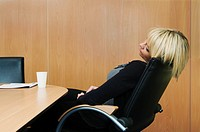 Woman relaxing in boardroom