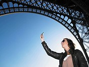 Woman taking picture of Eiffel tower