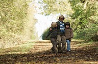 Three boys walking down country lane