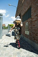 Young woman in trendy clothing walking on sidewalk, rear view