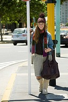 Young woman in trendy clothing standing on sidewalk, full length portrait
