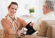 Nurse taking senior man's blood pressure