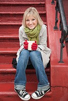 Woman drinking hot chocolate on front stoop