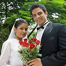 Portrait of a newlywed couple holding a bouquet of flowers and smiling