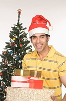 Portrait of a man holding Christmas presents and smiling