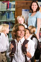 Elementary school boy with teacher and pupils in library
