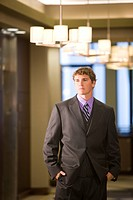 Close_up portrait of confident young businessman standing in modern lobby