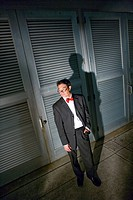 High angle portrait of Asian businessman standing in corridor