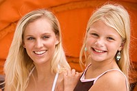 Close_up of mother and daughter smiling outdoors