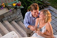 High angle view of young couple with champagne on garden steps