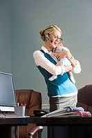Portrait of young businesswoman standing in office holding baby and on the phone