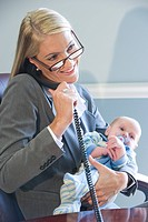 Young businesswoman holding baby in arms and on the phone at work