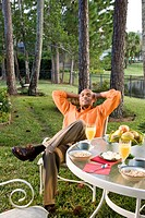 Portrait of African American man sitting at breakfast table in garden