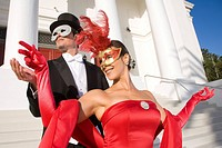 Couple in masquerade costumes standing outside theater