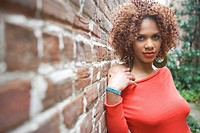 Portrait of stylish African American woman leaning against brick wall