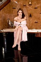 Portrait of woman in pink bathrobe sitting in bathroom next to bathtub