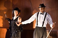 Portrait of African American man holding hand of flapper girl in 1920s speakeasy