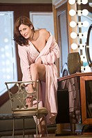 Portrait of woman in pink bathrobe standing in bathroom stroking leg