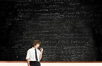 Boy with apple by blackboard
