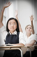 School students with hands raised